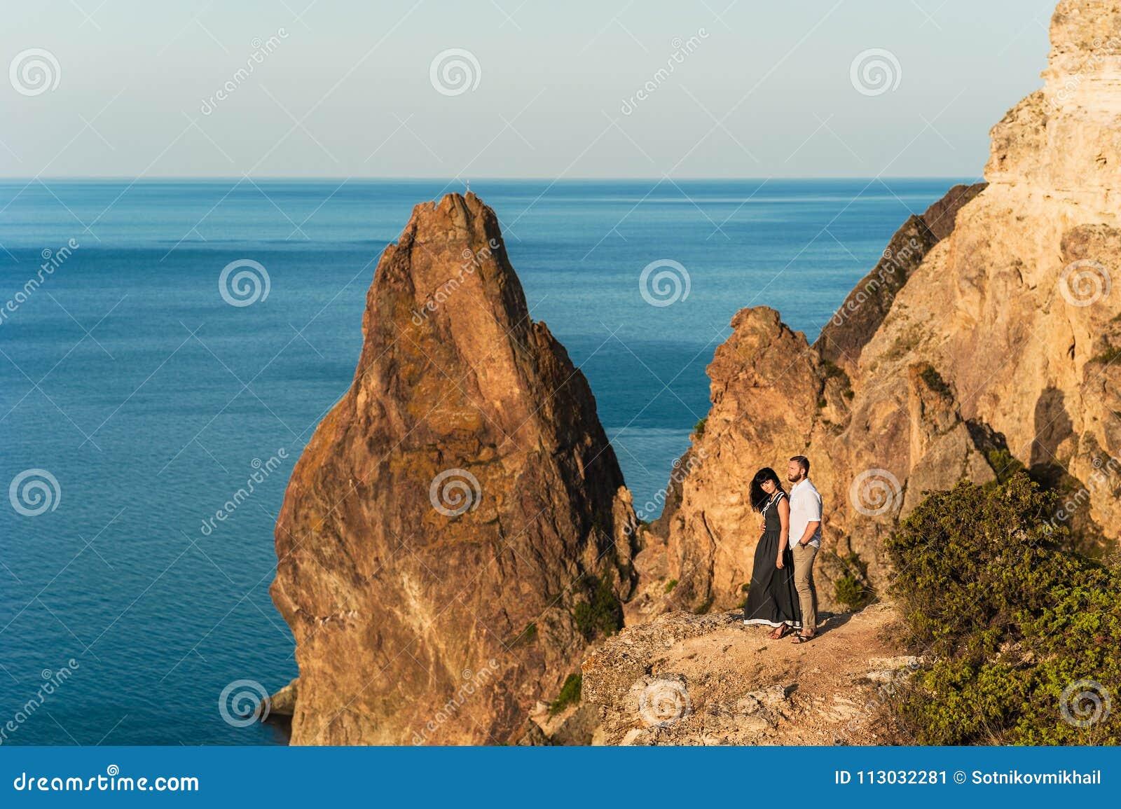 Individuo y muchacha en el mar que abraza al borde del acantilado
