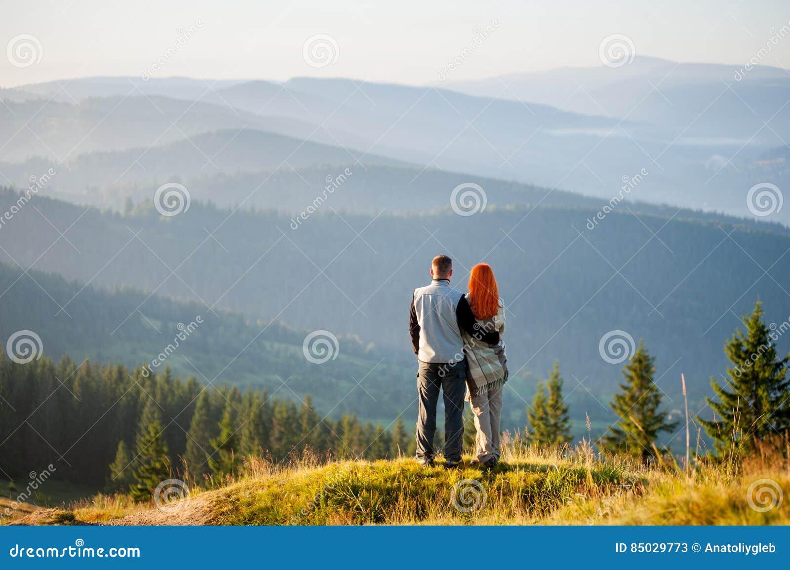 Individuo y muchacha felices en las montañas por la mañana