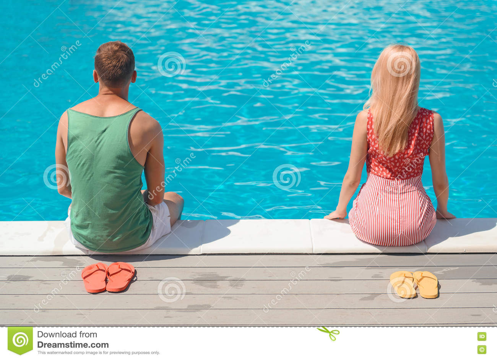 Individuo y muchacha que descansan cerca del agua