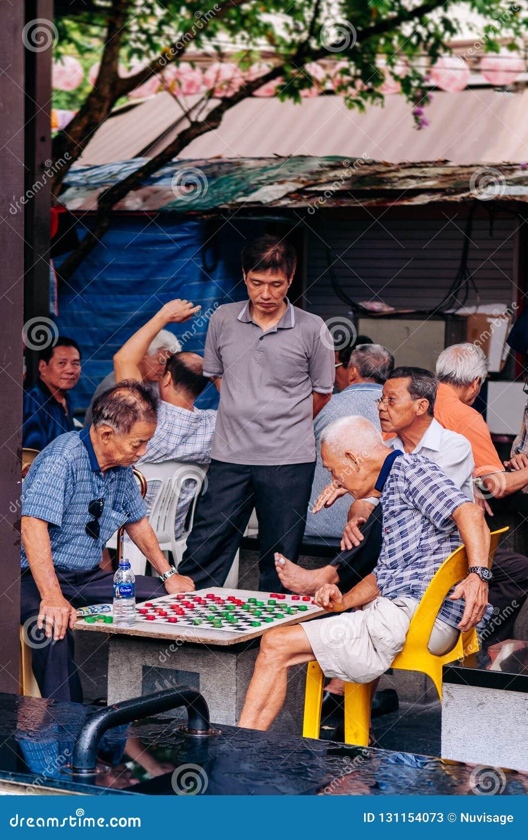Individuos mayores asiáticos que juegan a ajedrez con el grupo de los amigos