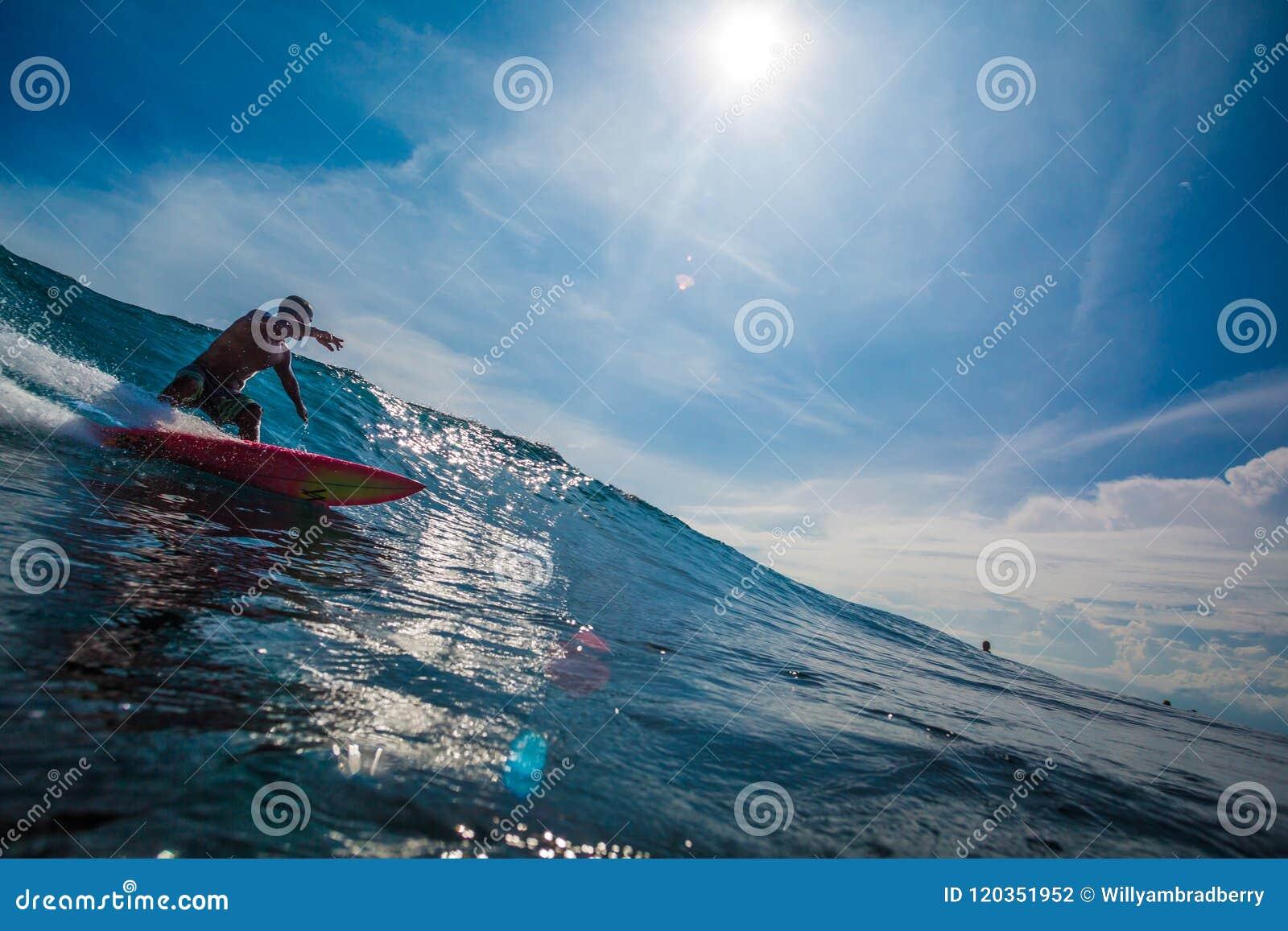 Indonesia, Bali, July 13 2016: A male surfer riding big blue oce