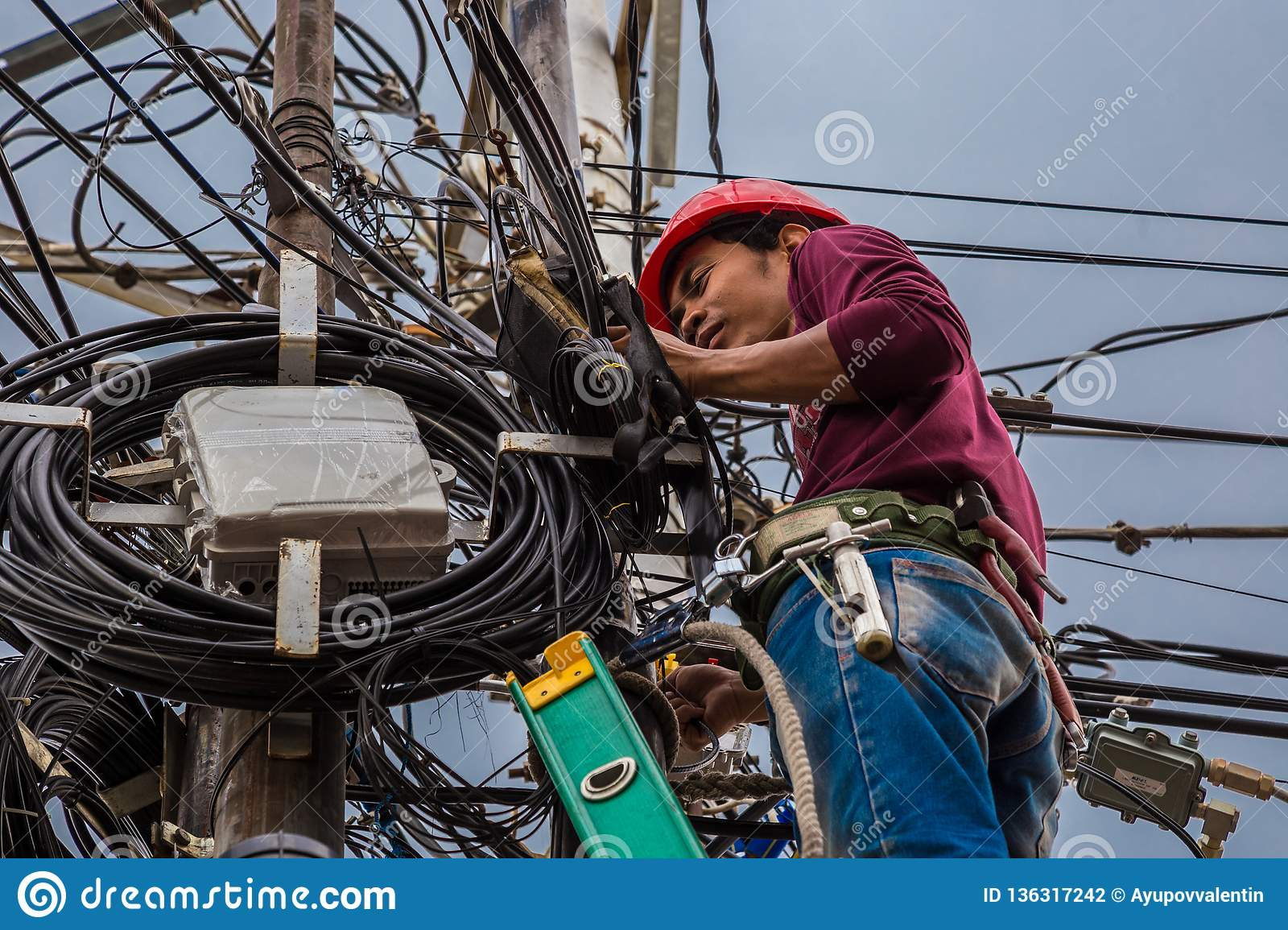 indonesian electrician repair workers are to fix the line of network cable  and wire on electric pole  jakarta, indonesia
