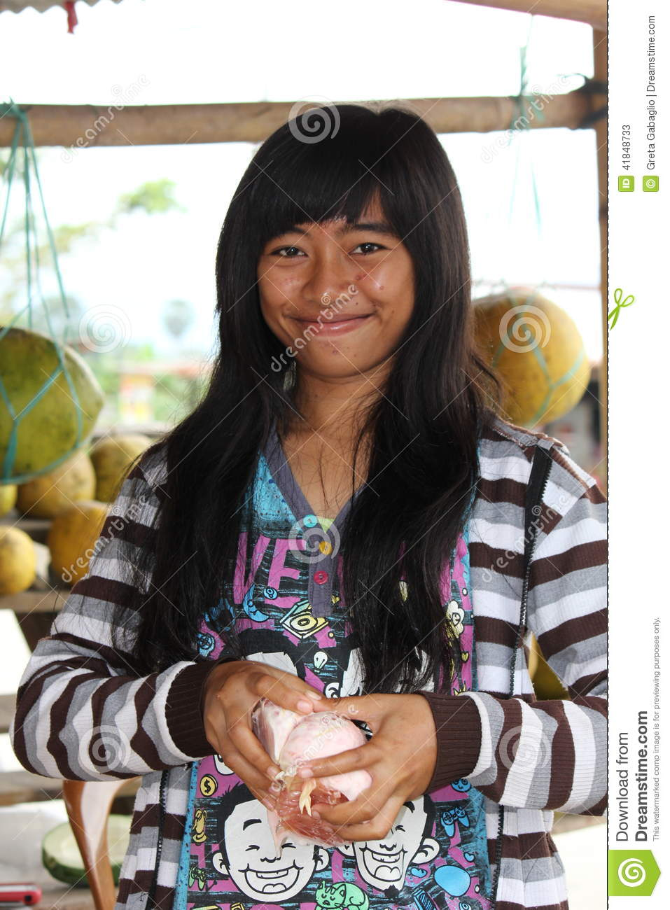 ... teen girl ins selling fruit at a litthe market along the street