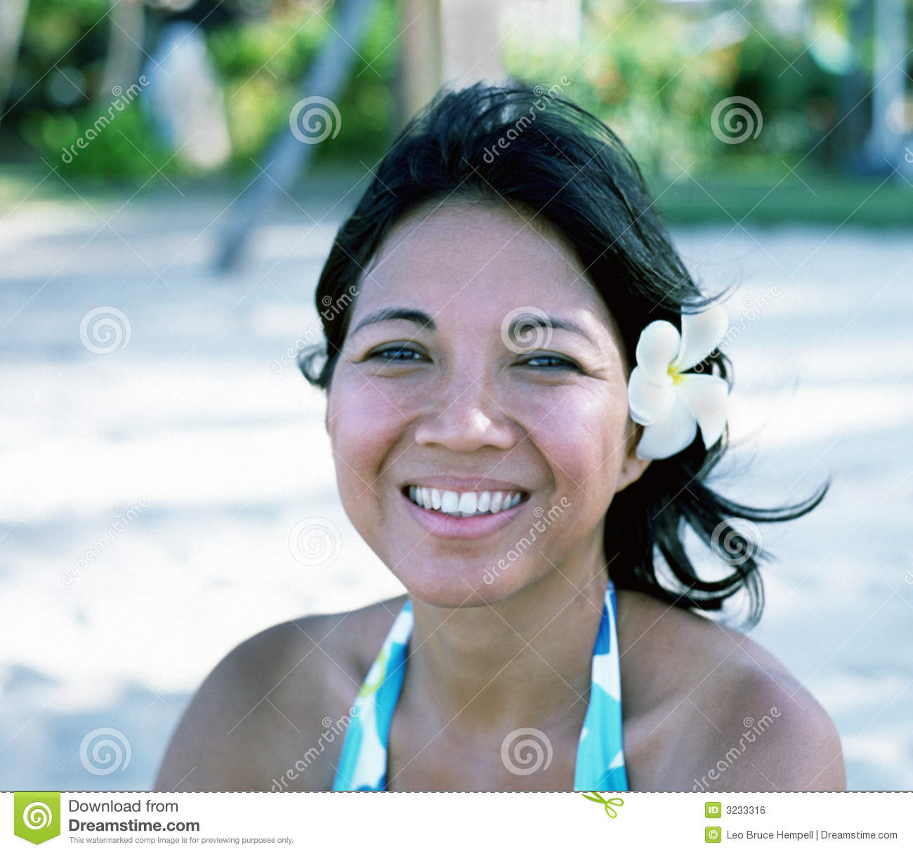 Indonesian beauty with a Frangipani flower in her hair looks out to ...