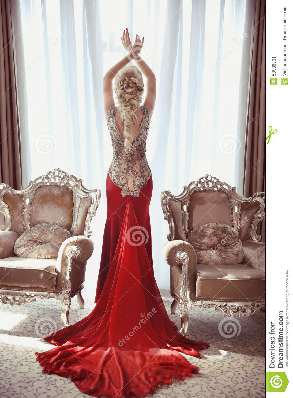 Indoor full length portrait of elegant blond woman in red gown with long  train of dress posing between two modern armchairs in front of window at  interior. 1b70cc525