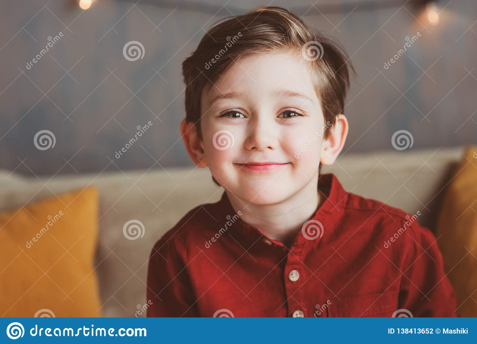 indoor portrait of happy handsome stylish child boy sitting on cozy couch