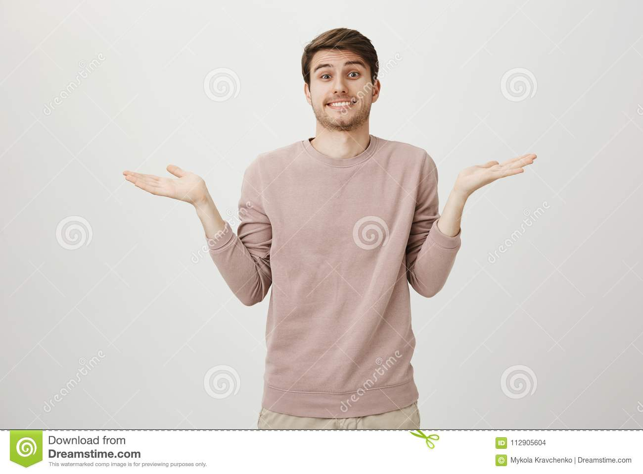 Indoor shot of attractive positive caucasian guy with bristle, shrugging with spreaded hands, being clueless, having no