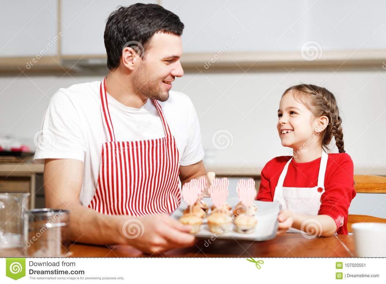Indoor shot of handsome man wears striped apron and his small pretty female kid hold hand made cakes, rejoices