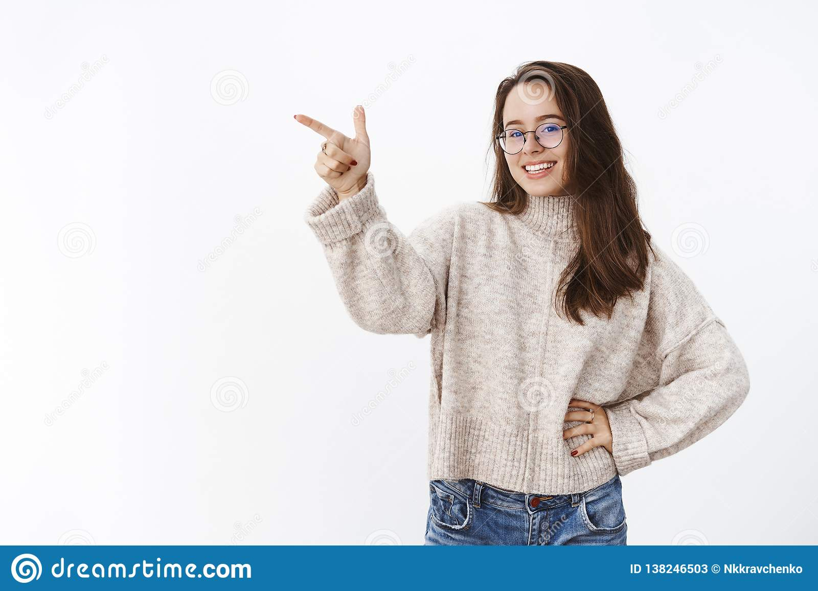 Indoor shot of happy carefree attractive female in glasses and sweater holding hand on waist, smiling and laughing as