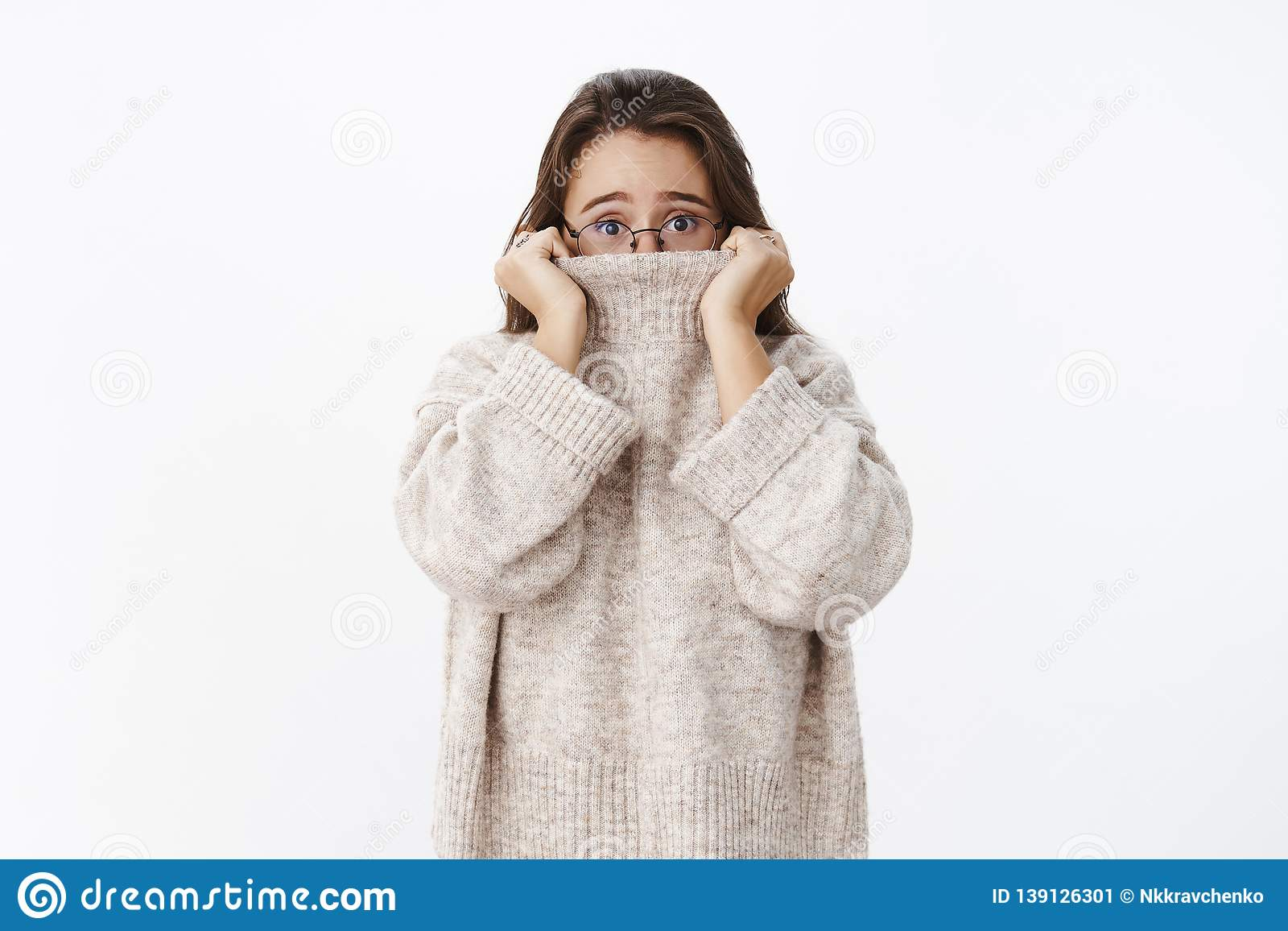 Indoor shot of insecure worried young cute woman in glasses with brown hair pulling collar of sweater on nose and