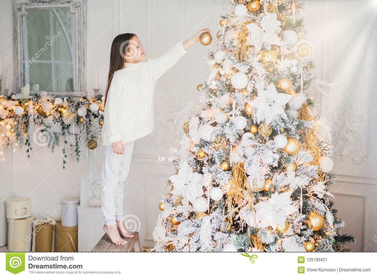 Indoor shot of small kid in white clothes, decorates New Year tree, stands on tiptoe, holds decoration in hands, does everything w