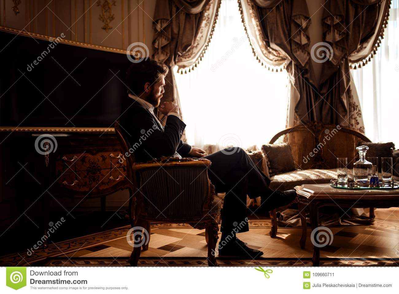 Indoor shot of thoughtful gorgeous businessman or entrepreneur wears black suit, sits in cozy room with luxurious