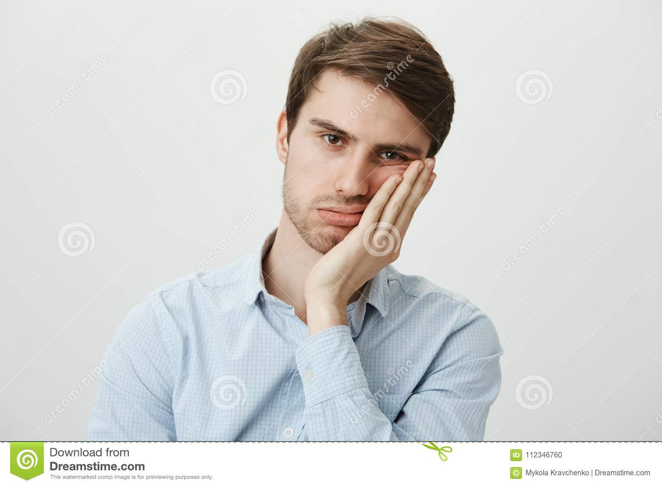 Indoor shot of upset irritated caucasian guy leaning on palm and sighing at camera, being bored and fed up of annoying