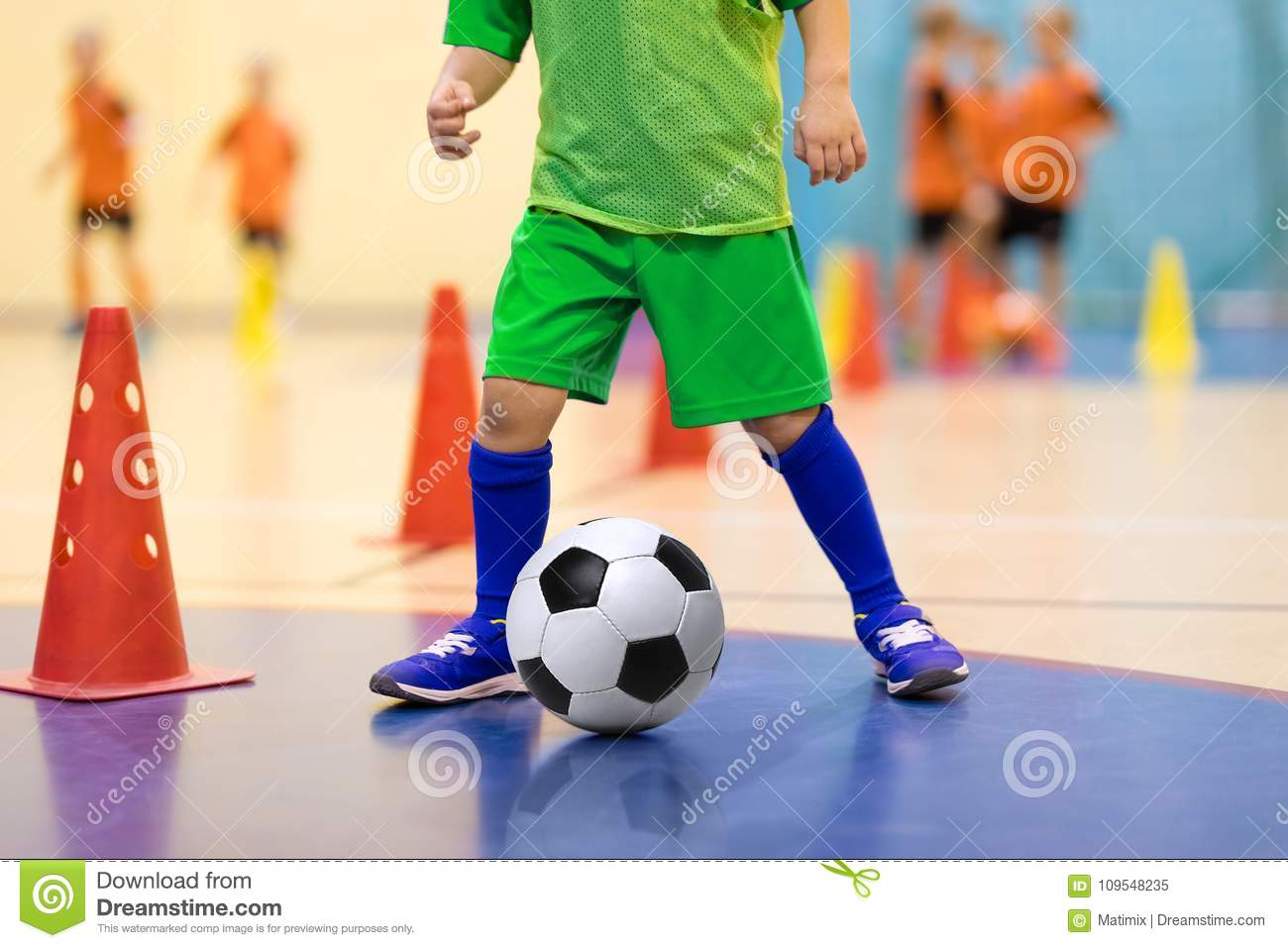 Indoor soccer young player with a soccer ball in a sports hall. Player in green uniform. Sport background.