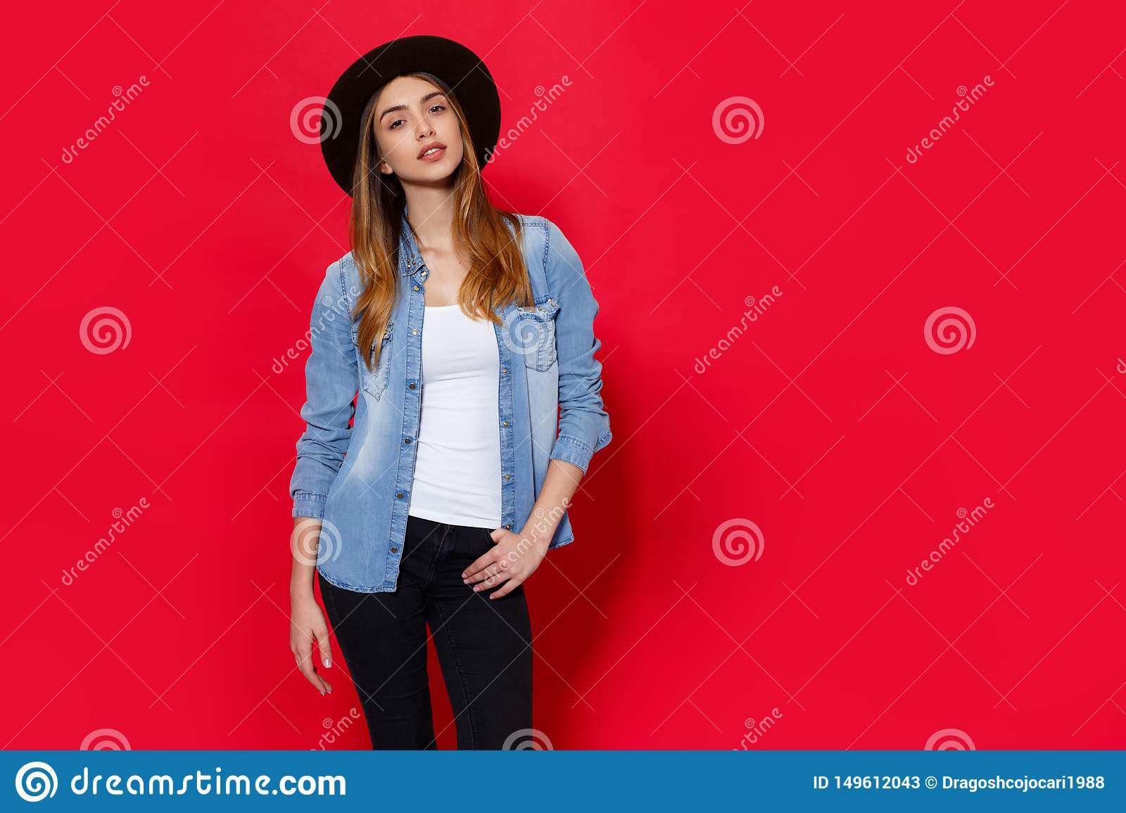 Close up indoor studio fashion portrait of gorgeous woman in stylish hat posing on bright red background. copy space.