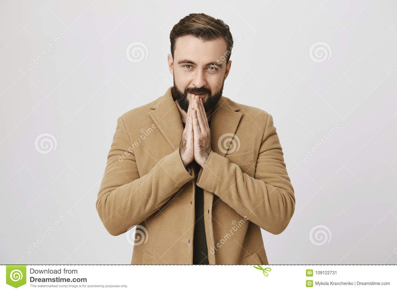 Indoor waist-up portrait of attractive bearded european model in coat, heating hands with warm breath, feeling cold