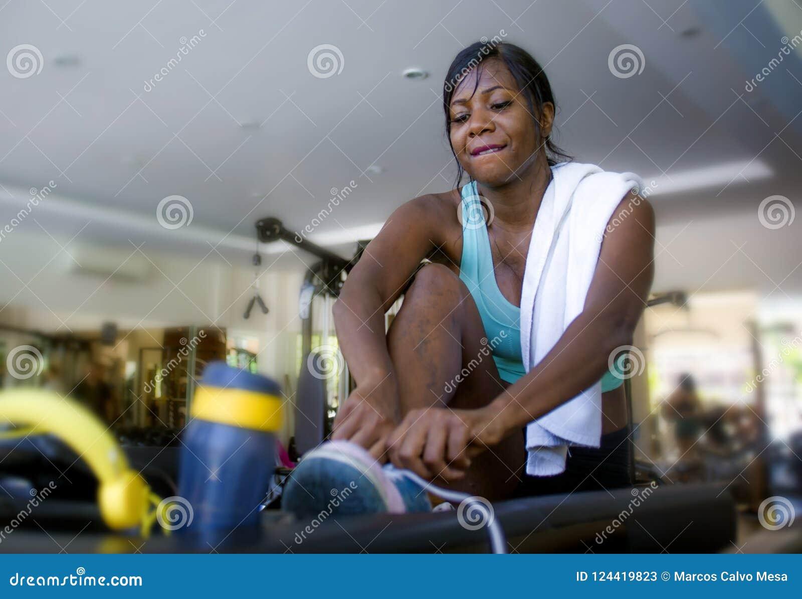 Indoors portret młody atrakcyjny i szczęśliwy czarny afro Amerykański kobiety szkolenie przy gym zasznurowywa sneakers podczas ki