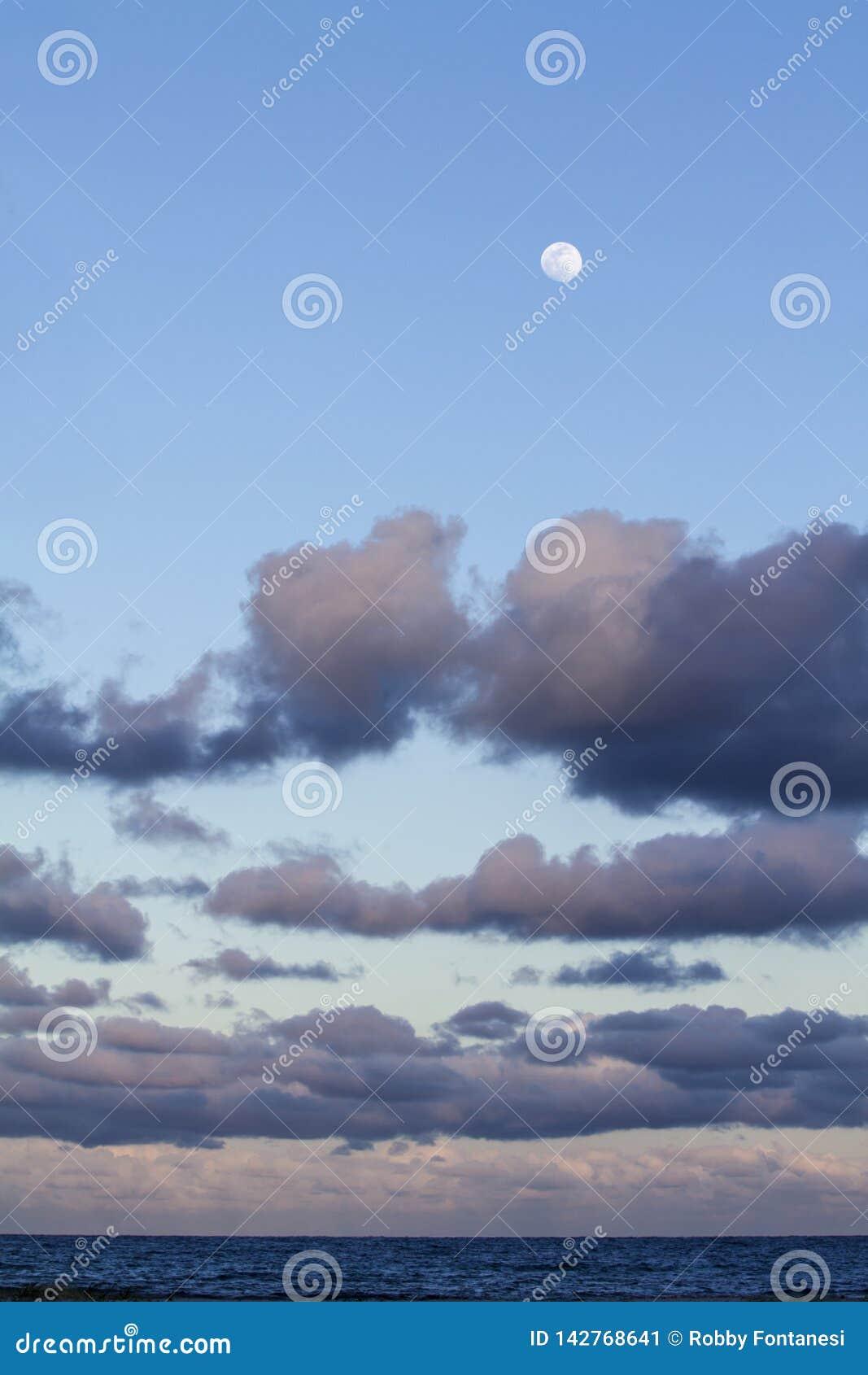 Indrukwekkende die hemel bij zonsondergang met een volle maan boven en lagen wolken met roze worden getint die neer aan de horizo