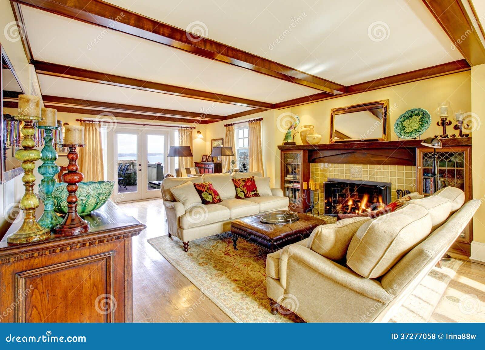 Openhaard In Woonkamer : Indrukwekkende woonkamer met plafondstralen en open haard stock