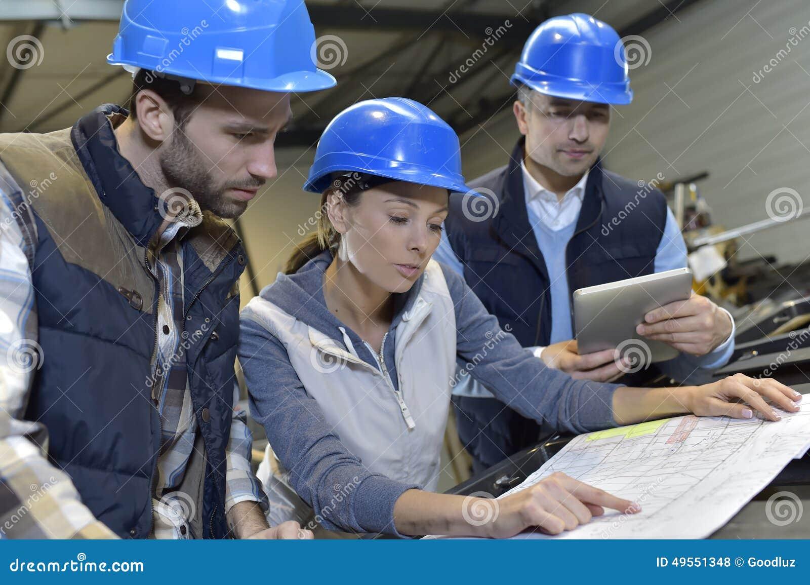 Industriële ingenieurs die en in mechanische fabriek samenkomen bespreken