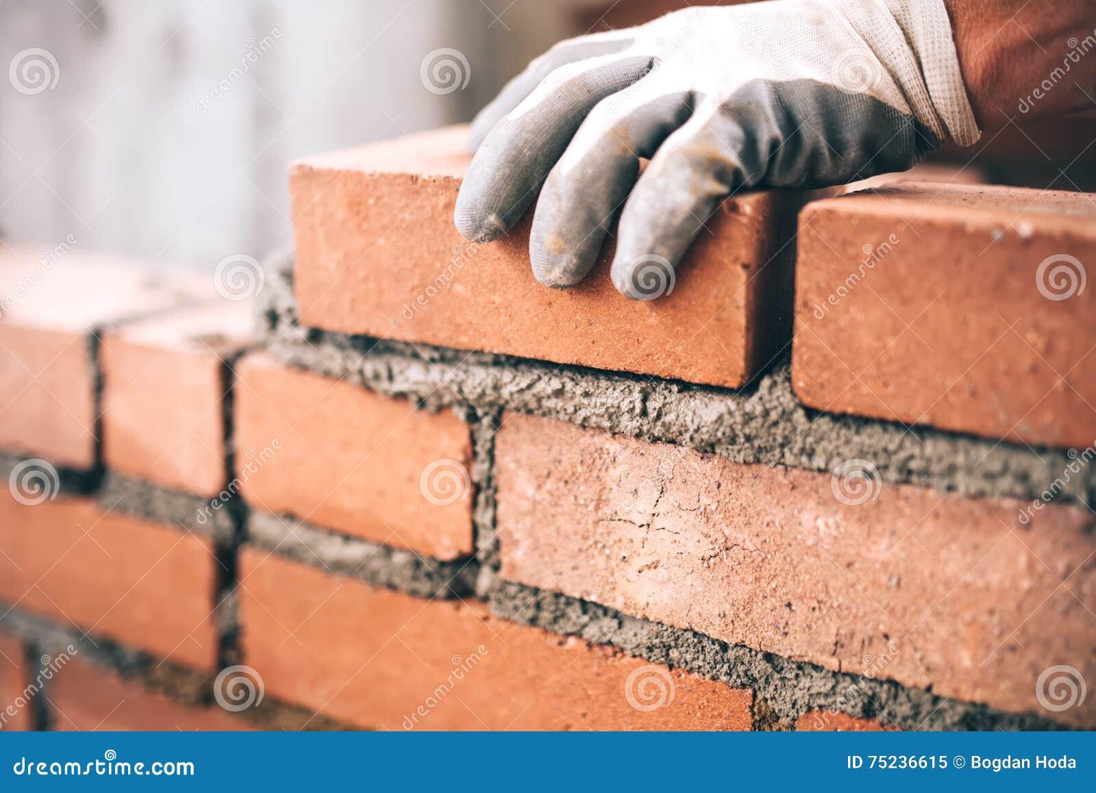 Industriële metselaar die bakstenen installeren op bouwwerf