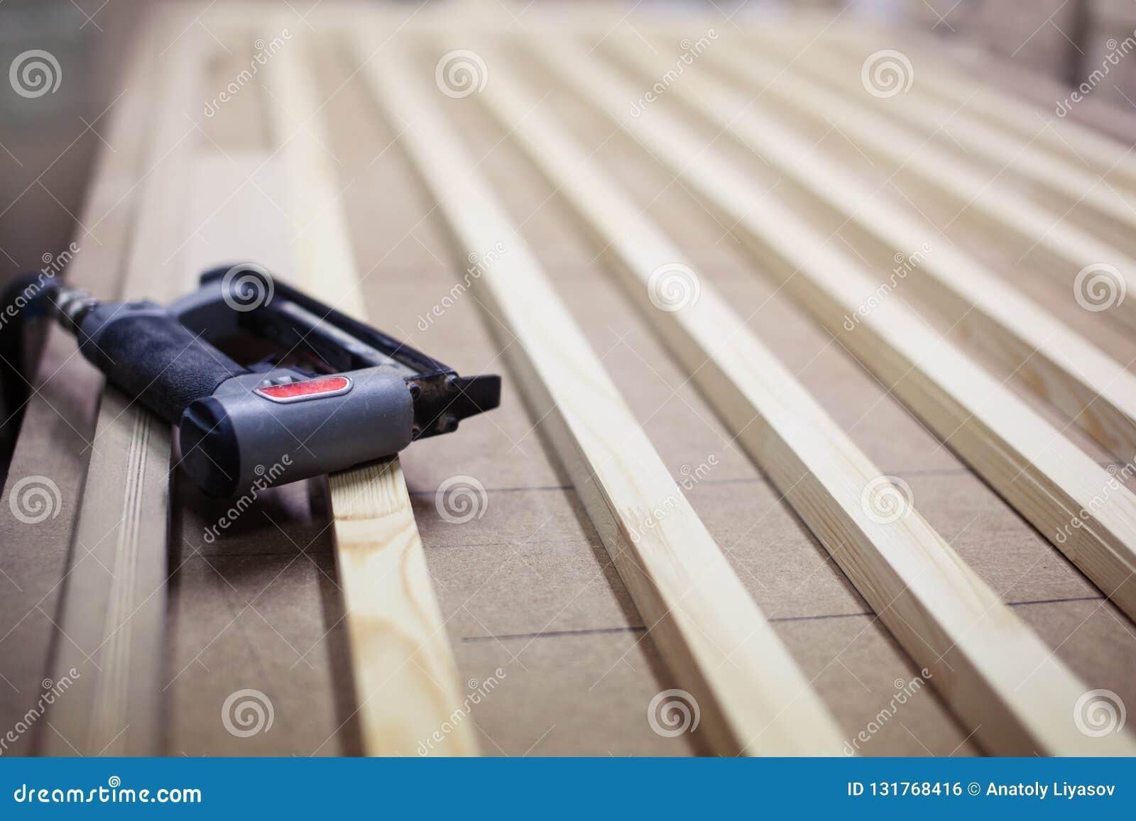 Industriële nietmachine op het houten kader van de latjesdeur