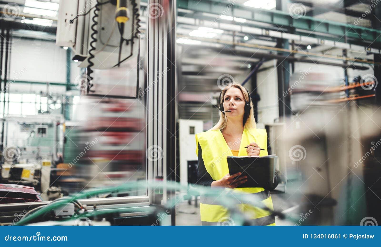 Industriële vrouweningenieur met hoofdtelefoon in een fabriek, het werken De ruimte van het exemplaar