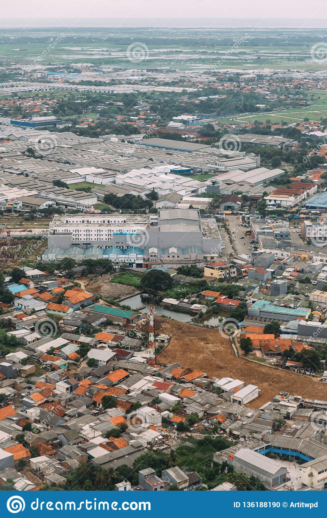 Industrial area in uptown of Jakarta, Indonesia. Aerial view of factories and houses from airplane