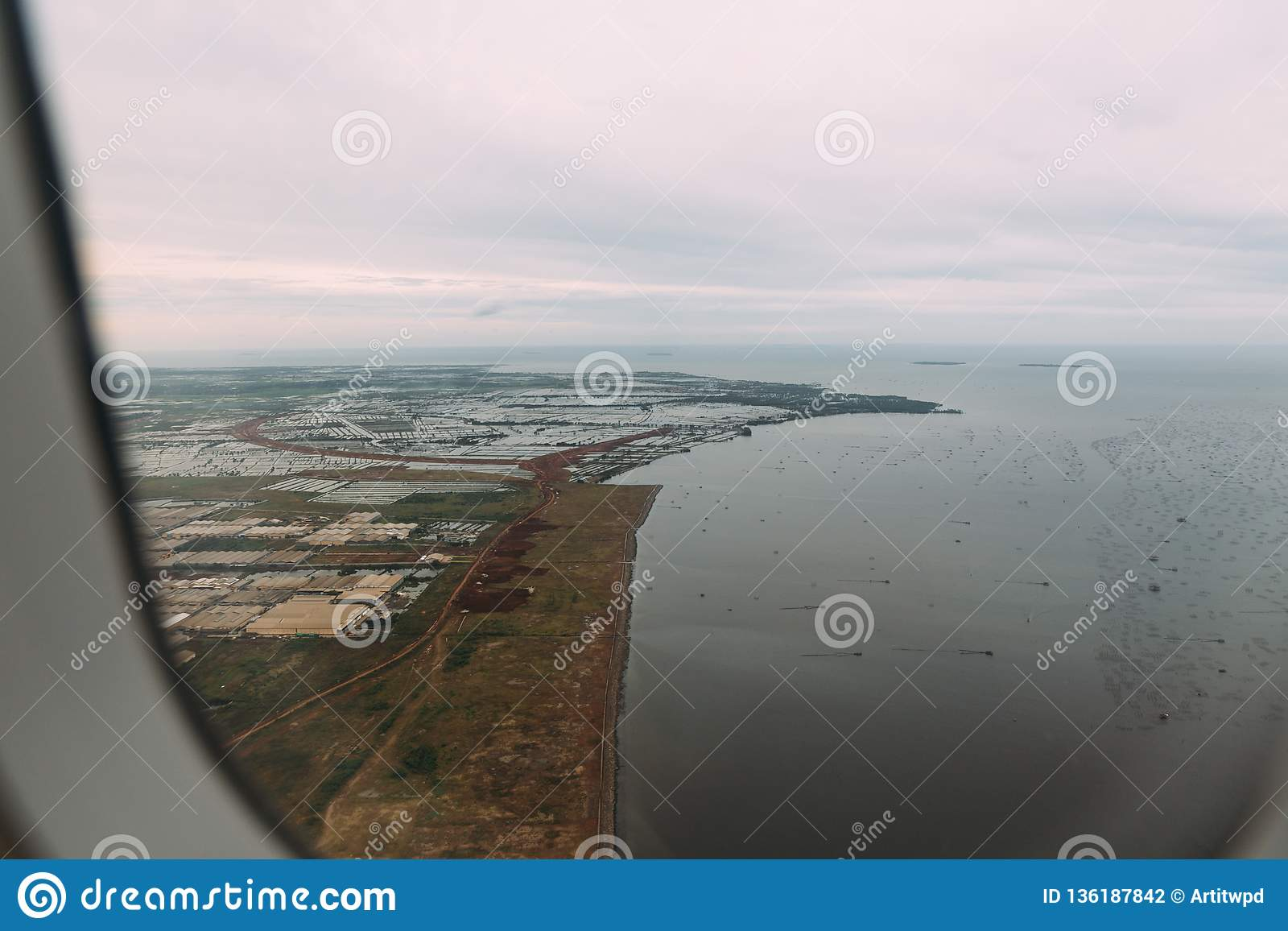 Industrial area in uptown near shore of Jakarta, Indonesia. Aerial view of factories, houses and sea from airplane