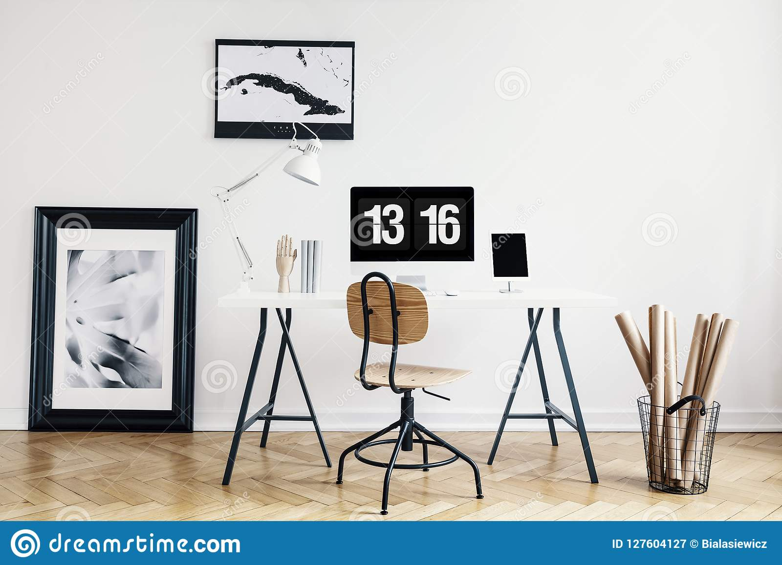 Industrial basket with kraft paper rolls and a framed poster in a white, minimalist home office interior of a freelancer architect