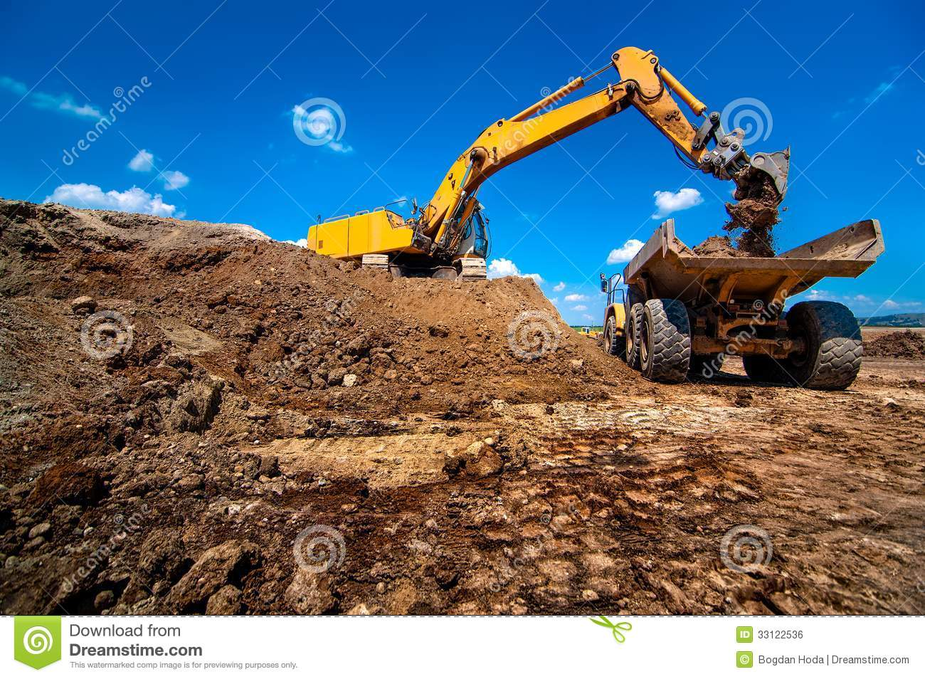 Construction Site Soil : Industrial excavator loading soil material royalty free