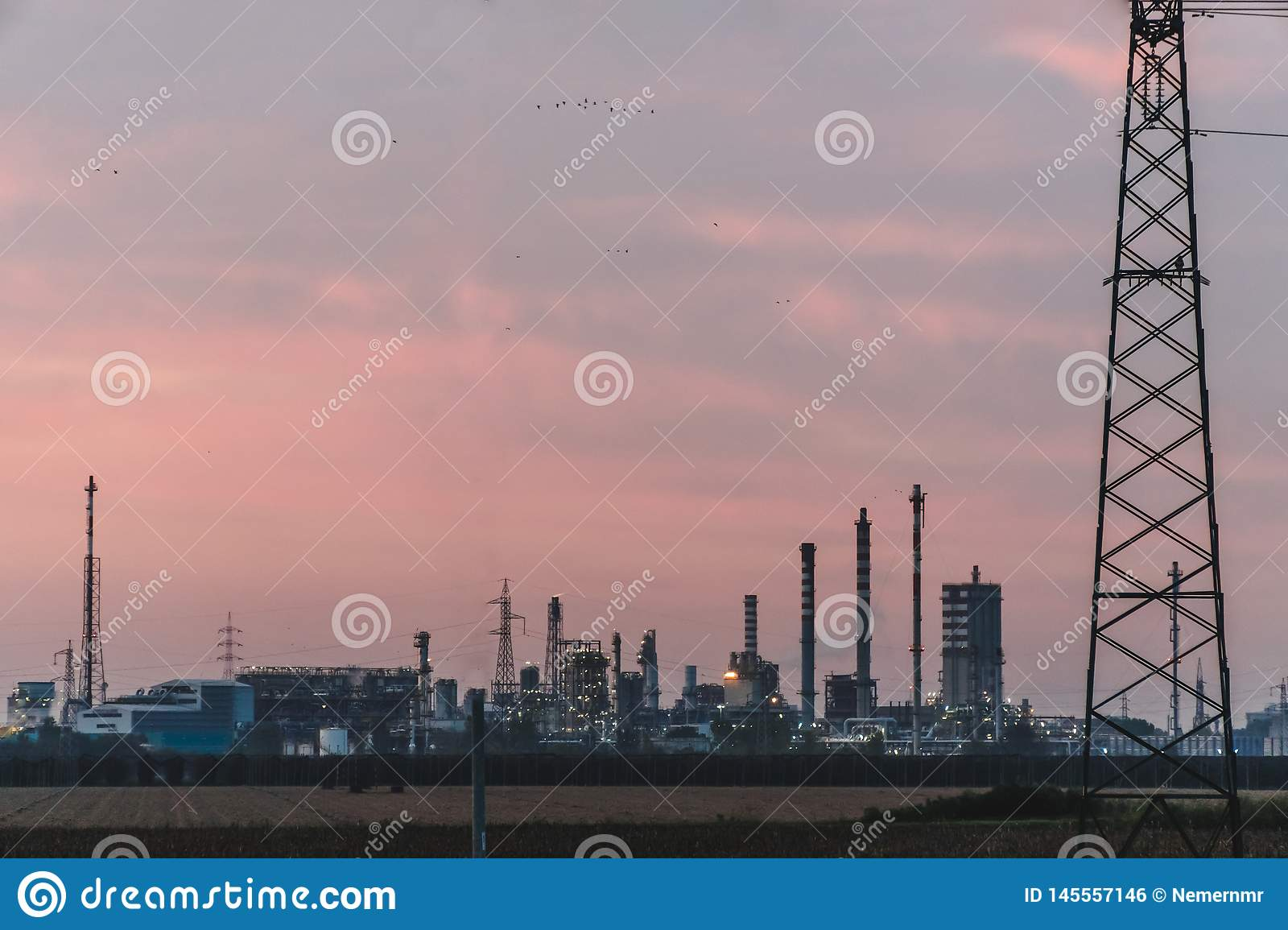 Industrial factory on sky sunset background, Petrochemical plant with sky evening background. Northern Italy work in a modern