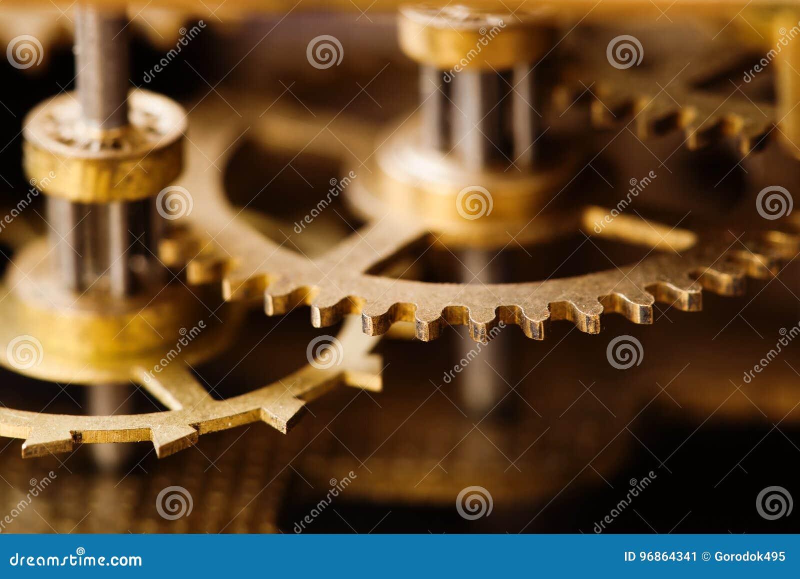 Industrial machinery bronze cog transmission macro view. Aged metal gear wheel teeth mechanism, shallow depth field