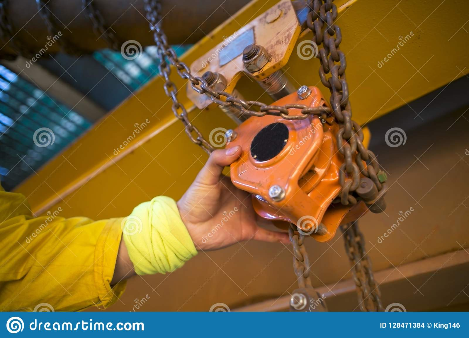 Industrial rope access inspector worker rigger hand commencing safety daily inspection check on lifting hoist chain block