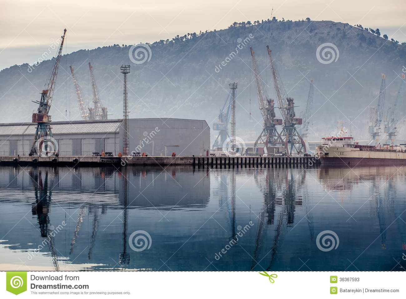 Industrial zone seaport with cranes in the fog