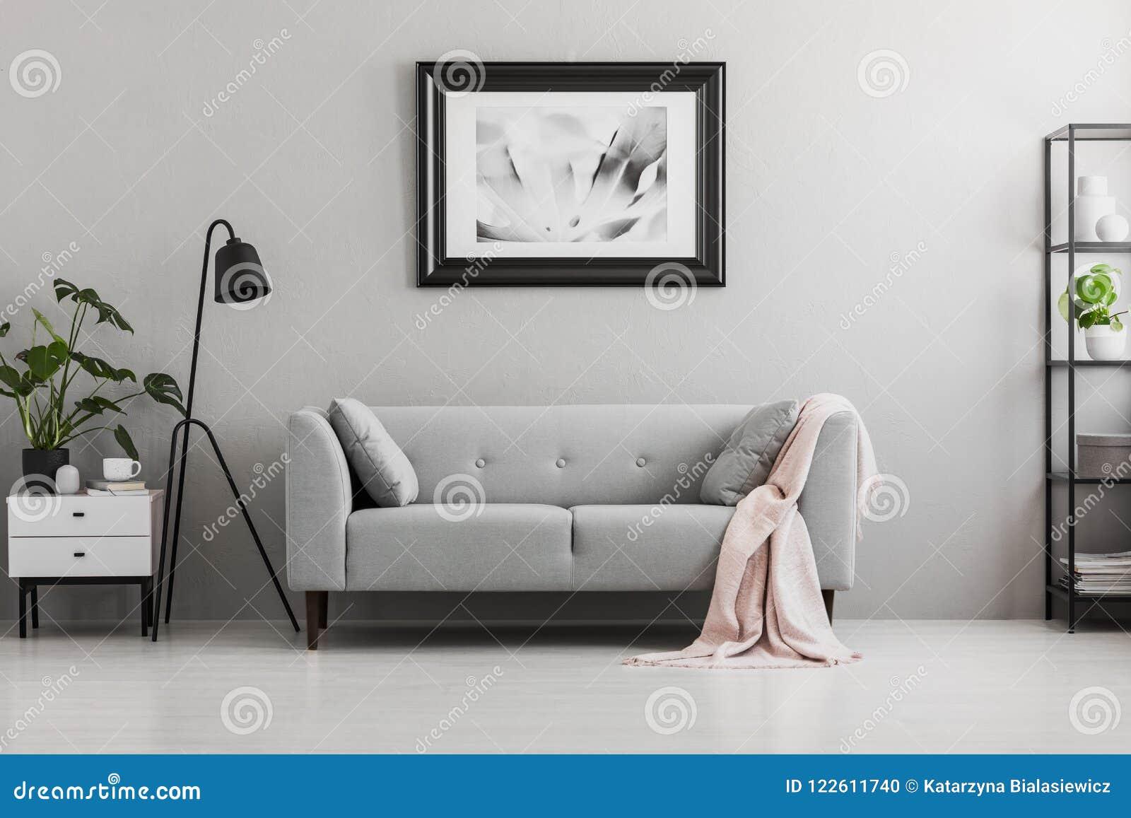 Industriell svart golvlampa och en rosa filt på en elegant soffa med kuddar i en grå vardagsruminre med stället för a