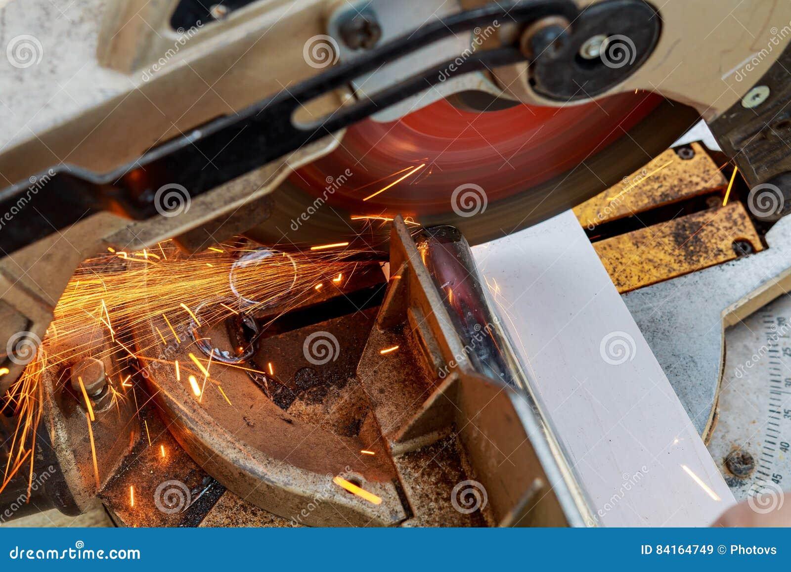 Industriell tekniker som arbetar på att klippa en metall och ett stål med sammansatt mitresågkors, runt blad