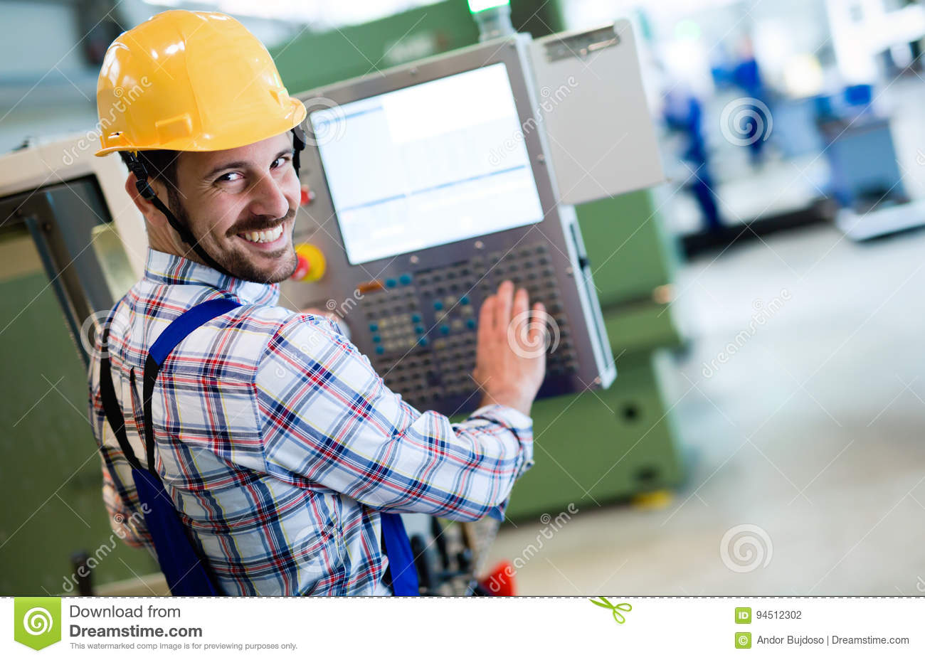 Industry Worker entering data in CNC machine at factory