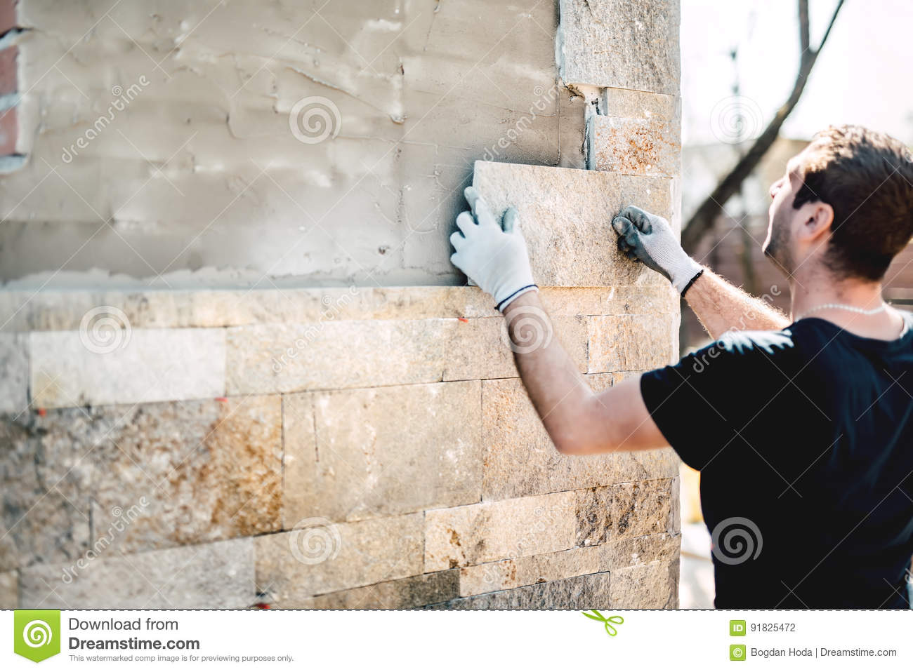 industry worker installing stone tiles on architectural house facade