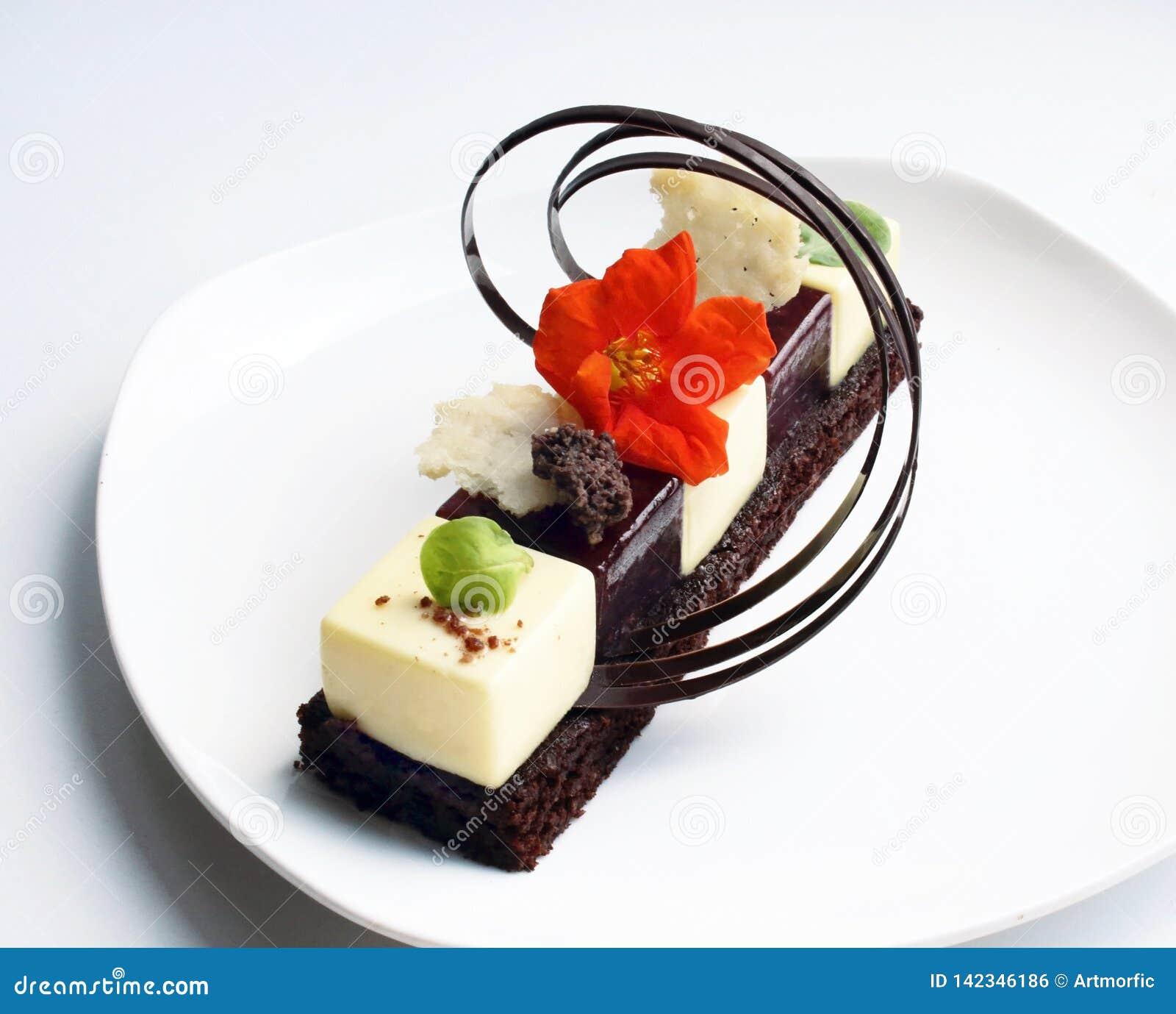Indywidualny deser z jadalną kwiatu i czekolady dekoracją na bielu talerzu