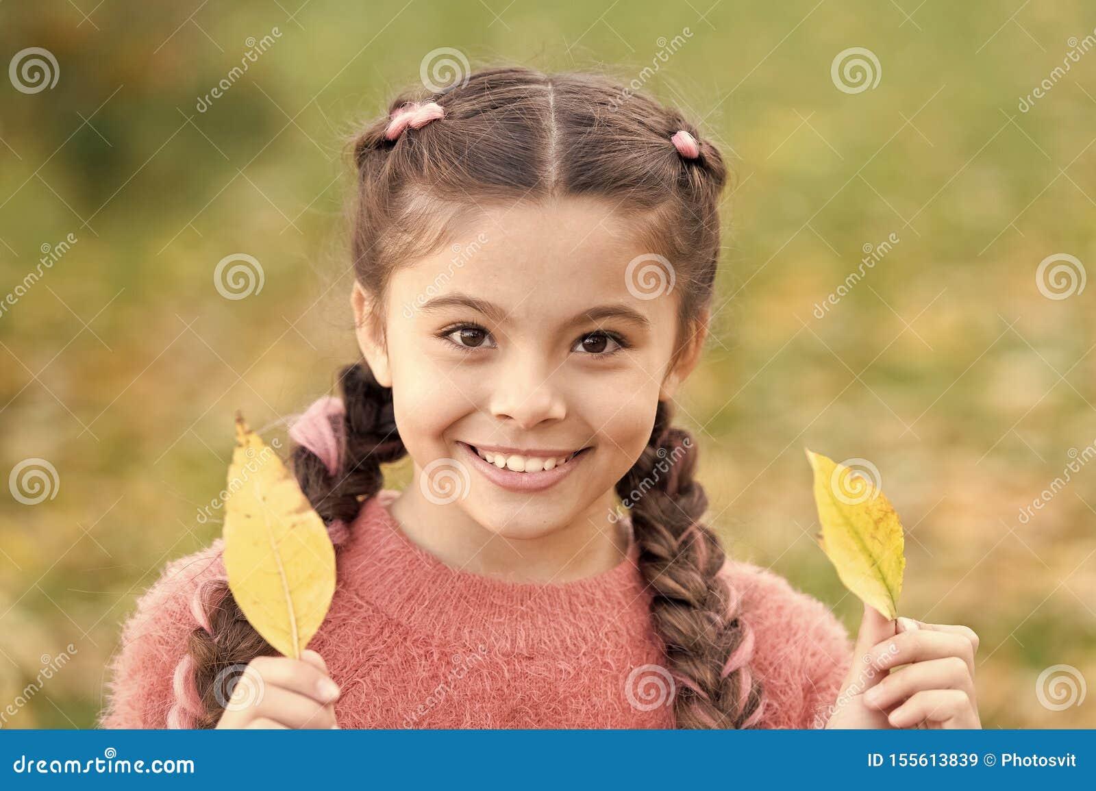 Inf?ncia feliz Tempo da escola Crian?a pequena com folhas de outono menina de sorriso nas folhas de outono da floresta do outono