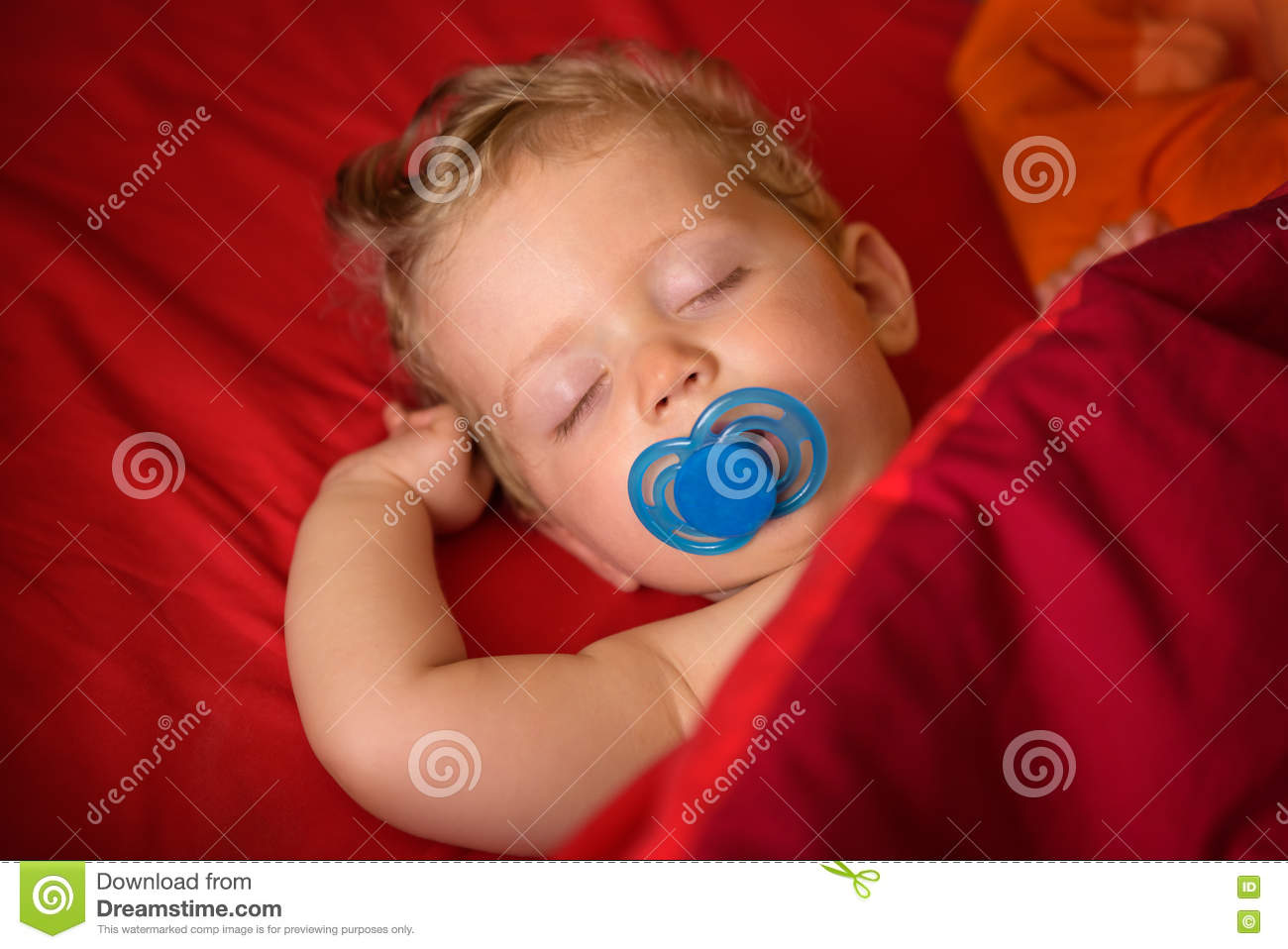 Infant boy eight month old sleeping with soother in his mouth in red backgroundclose up