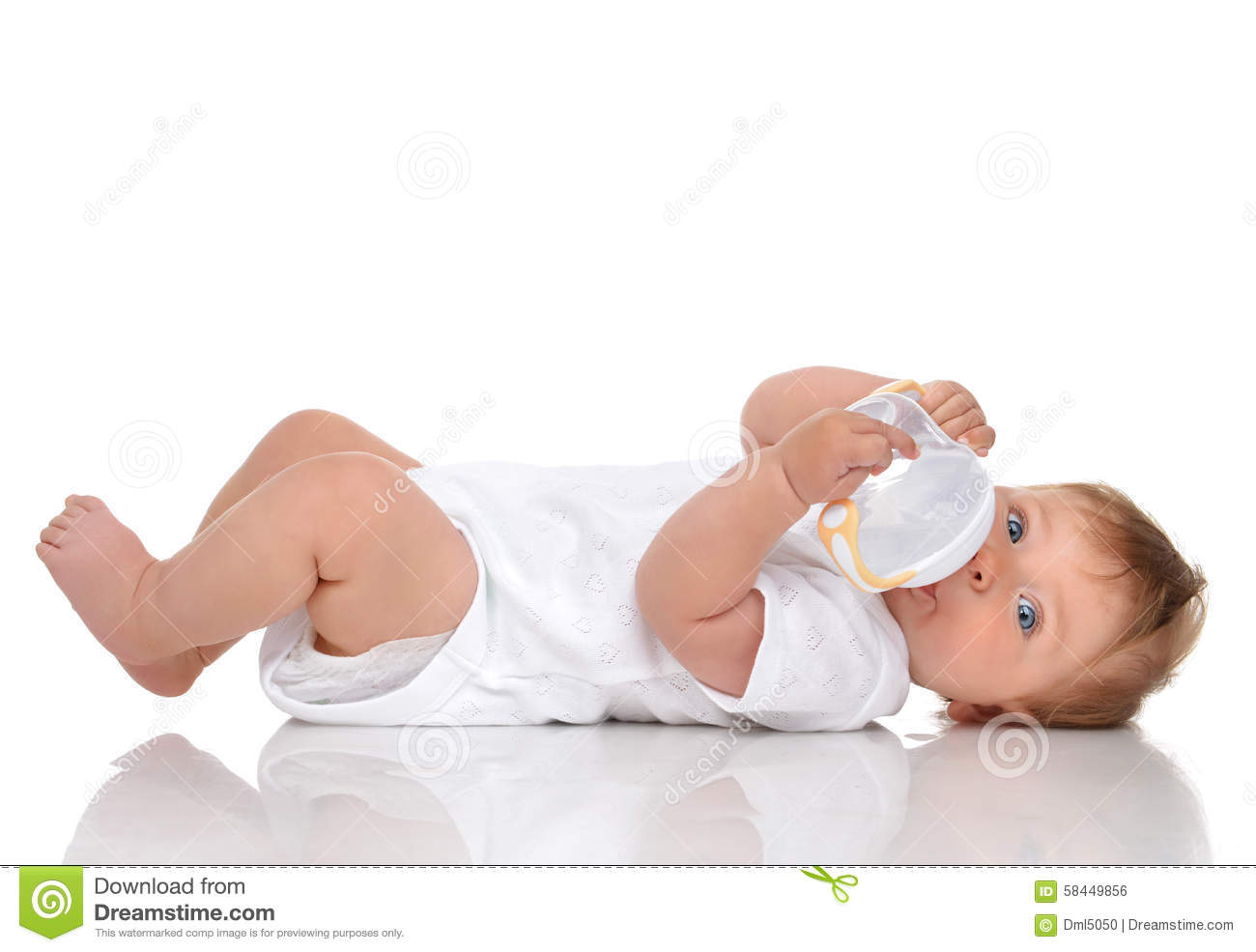 Infant child baby kid lying and drinking water from the feeding bottle ...