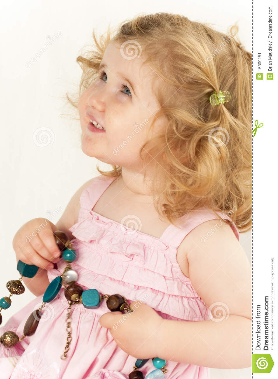 Infant girl holding a large bead necklace.