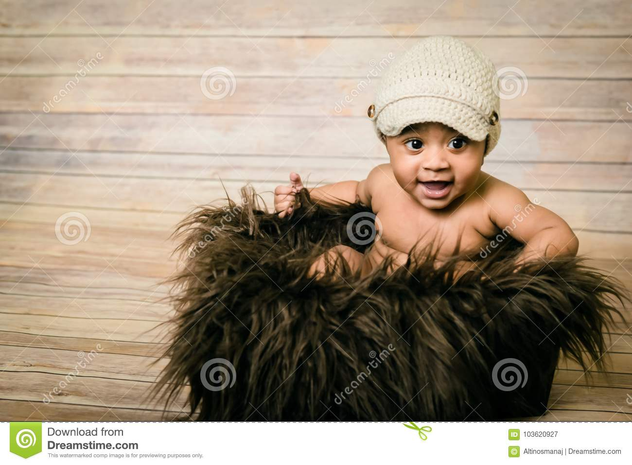 Infant mixed race healthy looking baby boy wearing knitted hat sitting in a fluffy furry basket wooden background modern studio sh