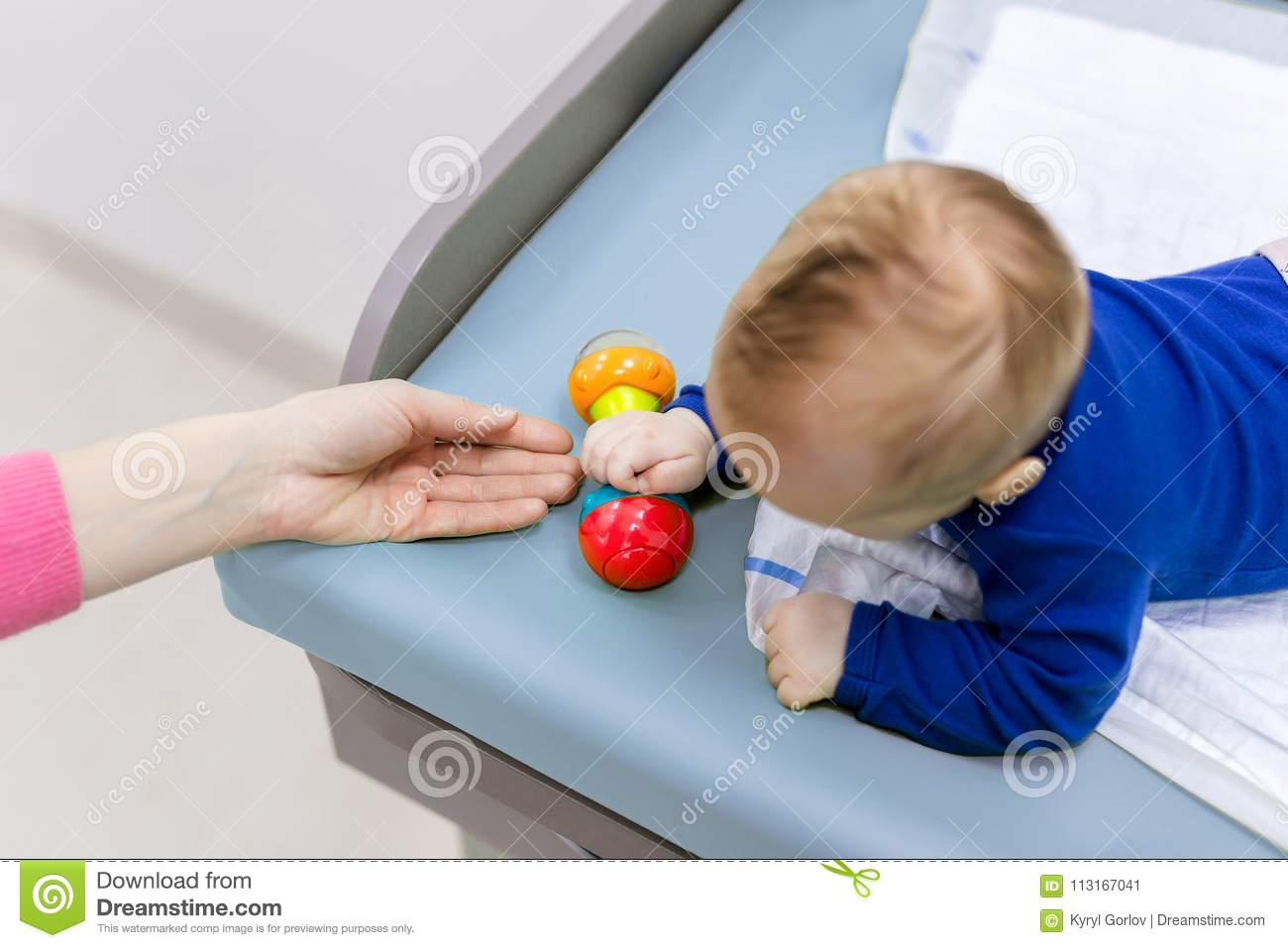 Infant With Mother Playing On Changing Table. Mom Giving Rattle Toy ...
