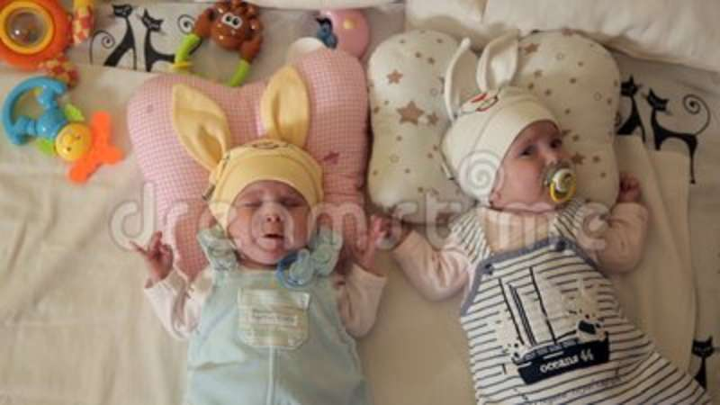 a4efb3bf4 Infants twins children in cute hats sleep in the arena and suck pacifier  pacifiers.