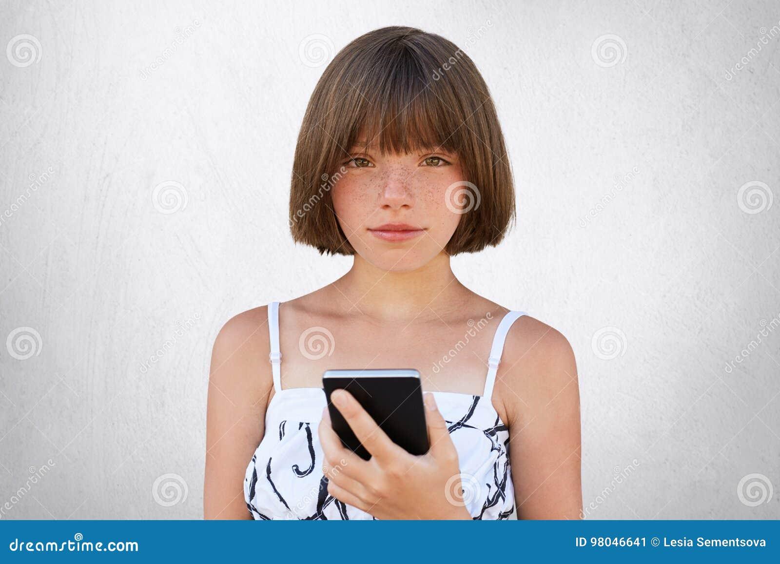 Infanzia nell era digitale Ragazza sveglia con la breve pettinatura alla moda, gli occhi incavati scuri e le lentiggini portanti