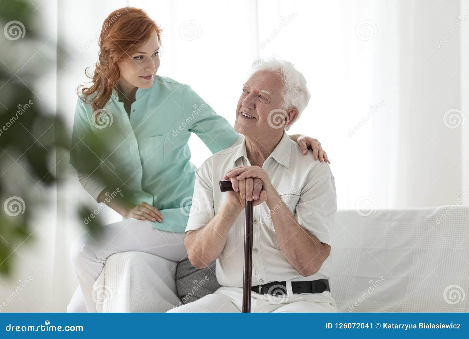 Infermiere amichevole ed uomo anziano sorridente con il bastone da passeggio in
