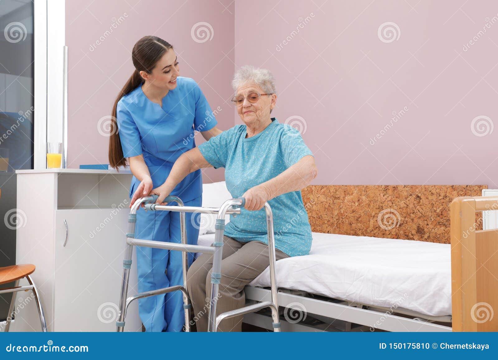 Infermiere che assiste donna senior con il camminatore per alzarsi dal letto